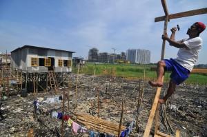 Sejumlah warga membangun kembali rumah mereka di lahan bekas kebakaran di kawasan Muara Baru, Jakarta Utara, Rabu (9/7).